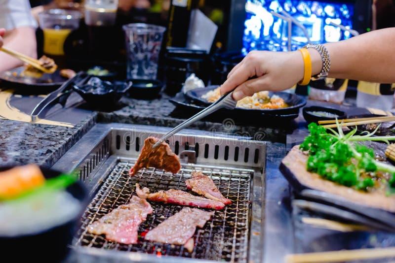 De selectieve nadruk aan de hand van de vrouw roostert wagyurundvlees in Japans geroosterd restaurant royalty-vrije stock afbeelding