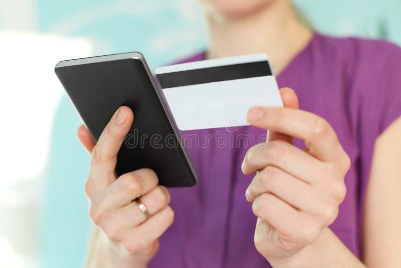De selectieve nadruk op vrouwen` s handen houdt moderne zwarte celtelefoon en plastic kaart, maakt het winkelen online of control stock foto's