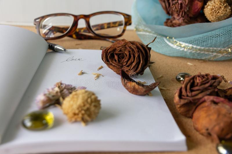 De selectieve nadruk vernietigde droog toenam op Witboekboek met droge bloemen en uitstekende zonnebril op cork oude achtergrond, royalty-vrije stock afbeeldingen