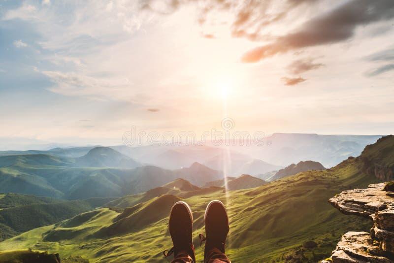 De Selfie do moderno pés do viajante das sapatas que relaxa nas montanhas do penhasco exteriores com as montanhas aéreas da opini imagens de stock