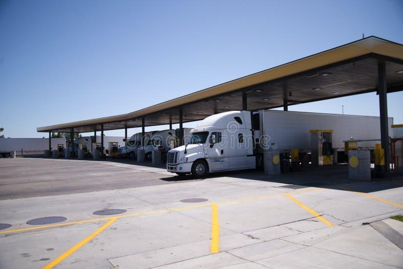 De semi Vrachtwagens met aanhangwagens zijn bij benzinestation voor diesel refu stock afbeelding