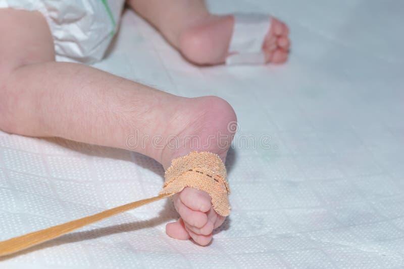 De sensor van impulsoximeter op de voet van pasgeboren baby bij het kinderen` s ziekenhuis stock foto