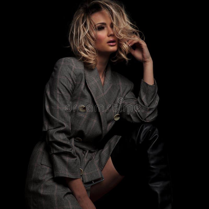 De sensuele blondevrouw in grijs kostuum kijkt aan kant royalty-vrije stock foto's