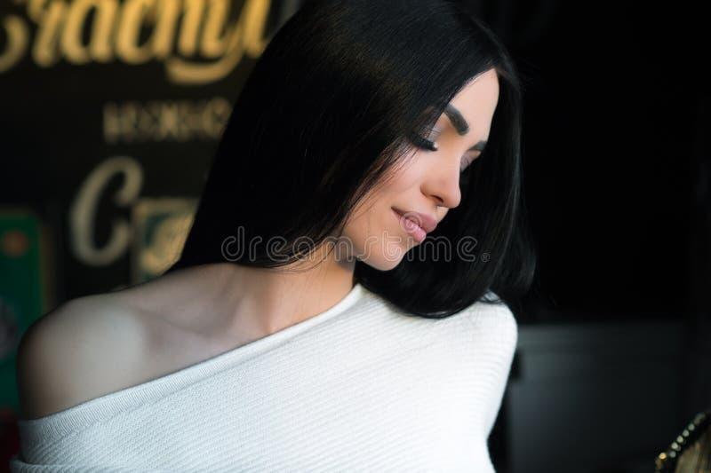 De sensuele donkerbruine vrouw in witte sweater zit in koffie royalty-vrije stock foto