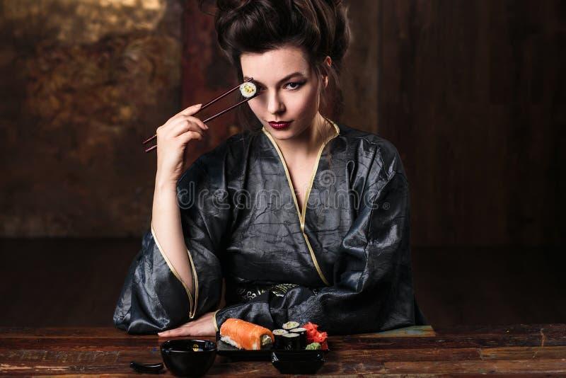De sensuele jonge vrouw in een geisha Aziatisch kostuum met maniermake-up en haarstijl eet sushi royalty-vrije stock afbeeldingen