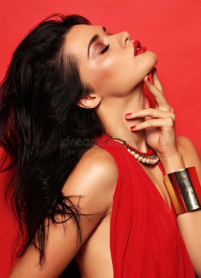 De sensuele vrouw met donker haar draagt elegante rode kleding en toebehoren stock foto