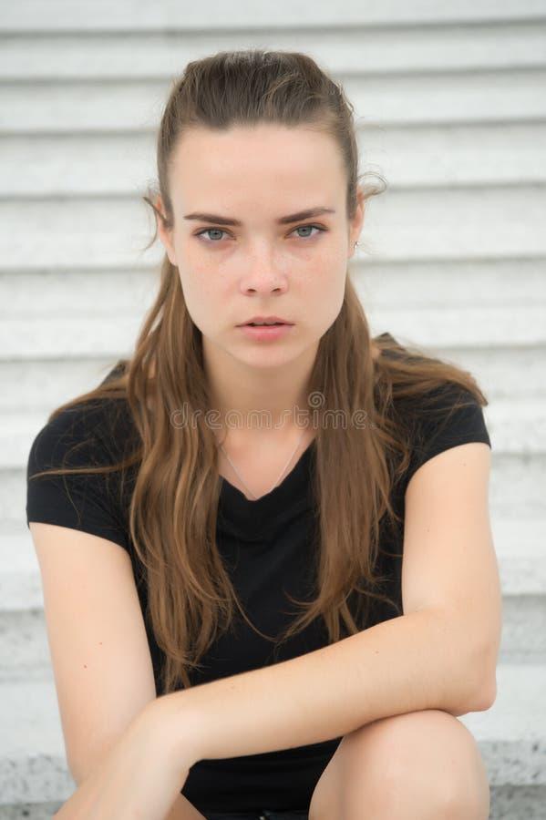 De sensuele vrouw ontspant op stappen in Parijs, Frankrijk Vrouw met lang haar op trap Het meisje met jongelui kijkt en schoonhei royalty-vrije stock afbeeldingen