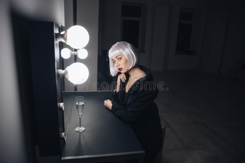 De sensuele zitting van de blondevrouw dichtbij spiegel met glas champagne stock fotografie