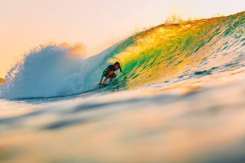 8 de septiembre de 2018 Bali, Indonesia Paseo de la persona que practica surf en onda del barril en la puesta del sol caliente El fotografía de archivo