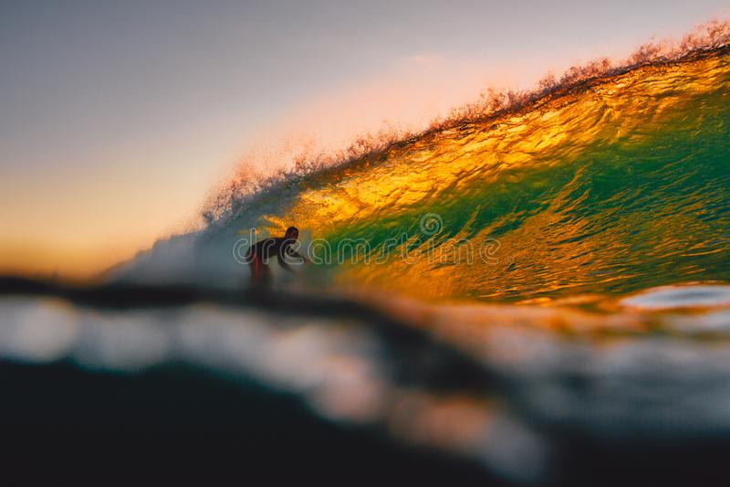 8 de septiembre de 2018 Bali, Indonesia Paseo de la persona que practica surf en onda del barril en la puesta del sol caliente El foto de archivo