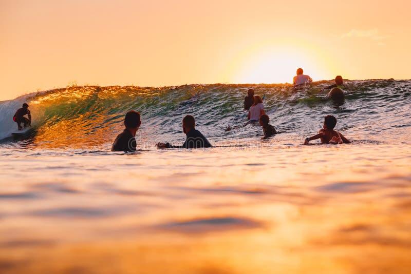 8 de septiembre de 2018 Bali, Indonesia Personas que practica surf y onda del barril en la puesta del sol El practicar surf profe fotos de archivo libres de regalías