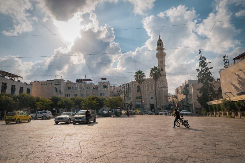 15 de septiembre de 2019. Belén, Palestina. La mezquita de Omar, ciclista que monta bicicletas y taxis foto de archivo