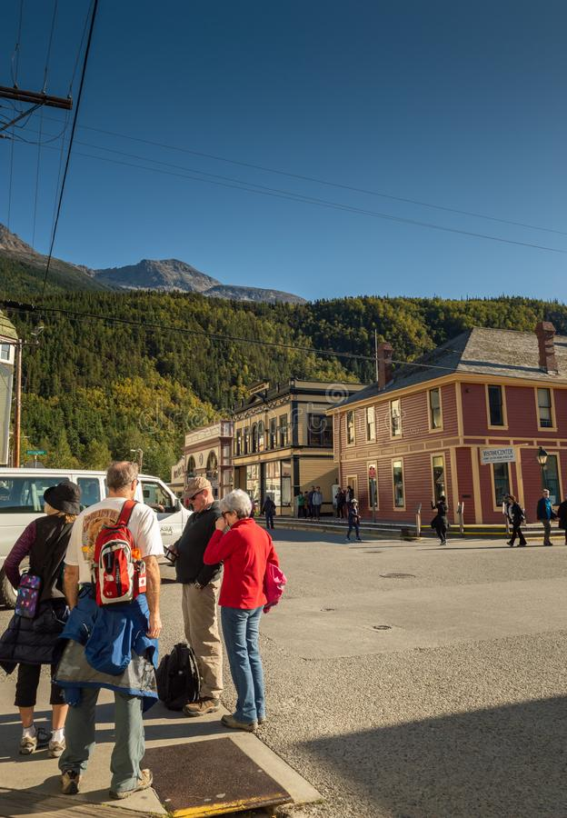 15 de septiembre de 2018 - Skagway, AK: Turistas en la esquina de Broadway y de la 2da avenida , Centro del visitante de NPS en f foto de archivo libre de regalías
