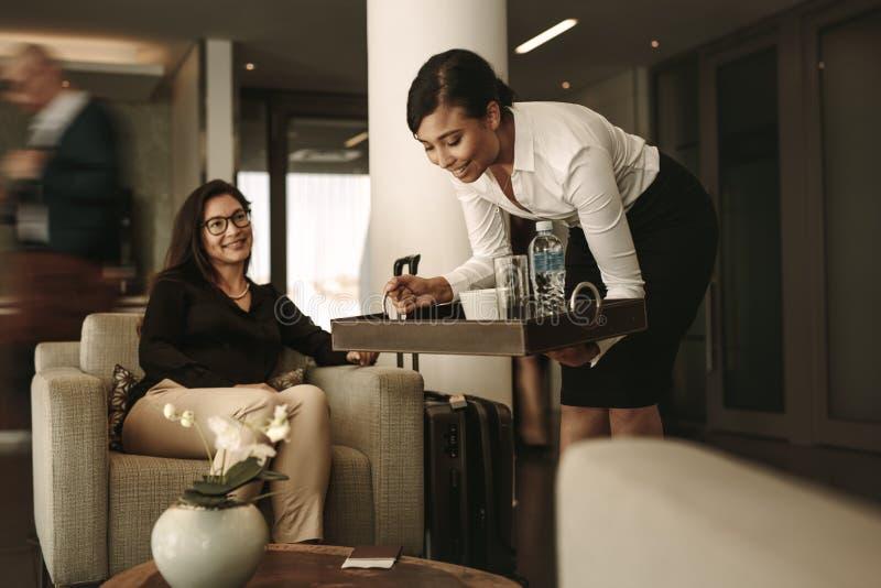 De serveerster dienende koffie van de luchthavenzitkamer aan vrouwelijke passagier stock afbeelding