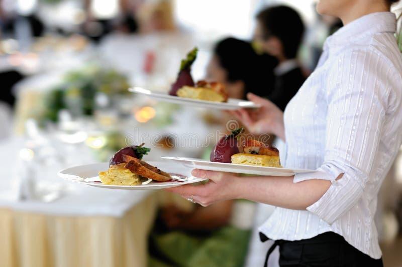 De serveerster draagt drie platen royalty-vrije stock foto