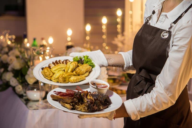De serveerster draagt twee platen met vleesschotel royalty-vrije stock foto's
