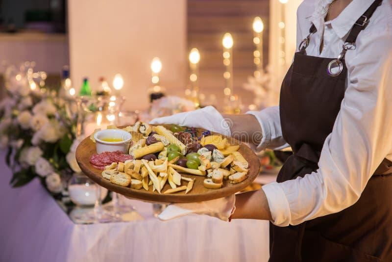De serveerster houdt een houten schotel met vlees en kaas royalty-vrije stock fotografie