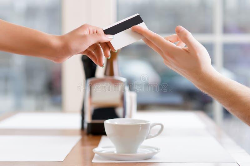 De serveerster neemt creditcard van een cliënt stock afbeeldingen