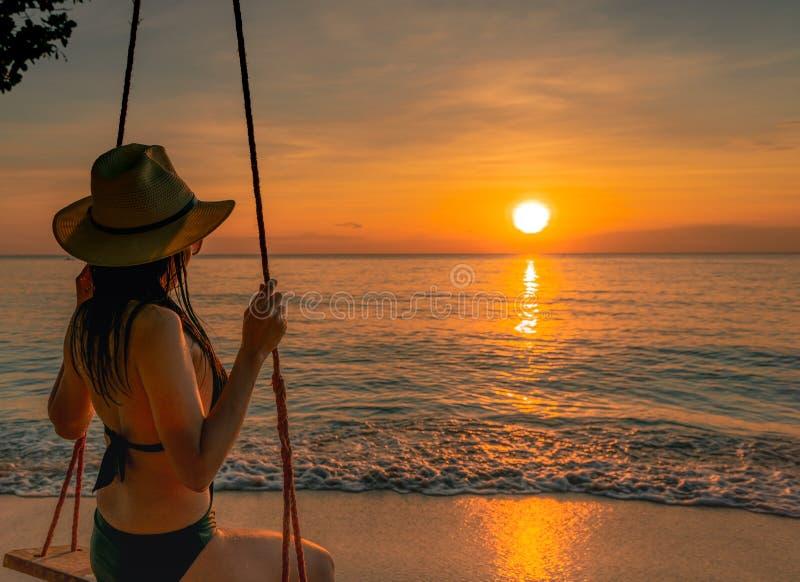 De sexy bikini van de vrouwenslijtage en de strohoed slingeren de schommeling bij tropisch strand op de zomervakantie bij zonsond royalty-vrije stock afbeelding