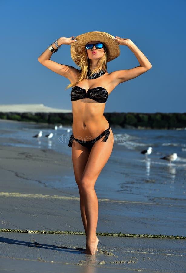 De sexy blonde jonge vrouw met een mooi slank cijfer looide lichaam het stellen vrij op het strand stock fotografie