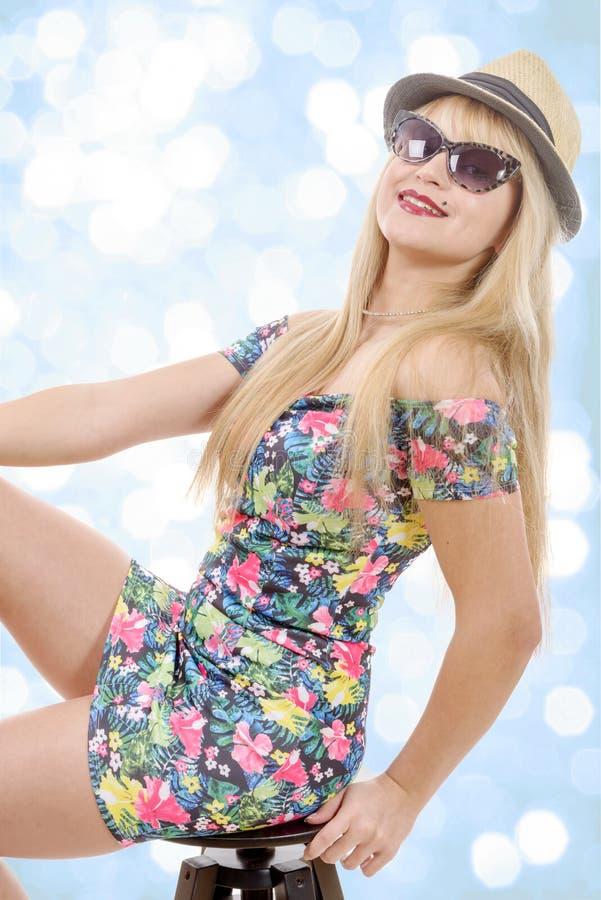 De sexy blonde vrouw die korte kleding dragen, zit op kruk stock afbeeldingen