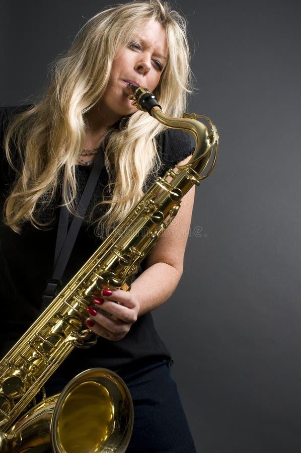 De sexy blonde vrouwelijke musicus van de saxofoonspeler stock afbeelding