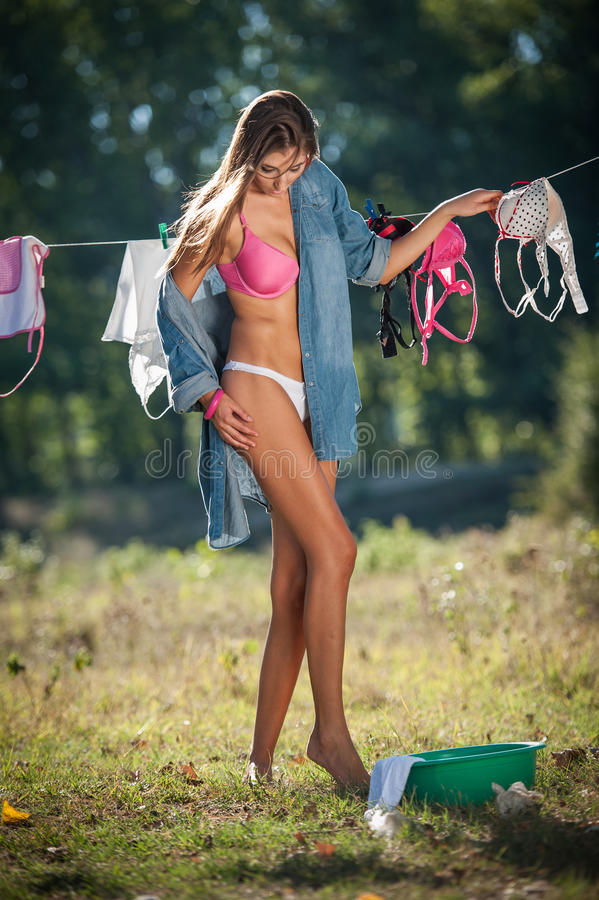 De sexy donkerbruine vrouw in bikini en overhemds het zetten kleedt zich om in zon te drogen Sensueel jong wijfje die met lange b stock afbeeldingen