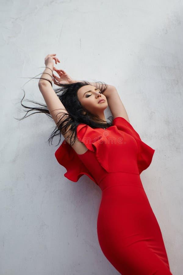 De sexy donkerbruine vrouw in rode kleding bevindt zich dichtbij de muren van ol royalty-vrije stock afbeelding