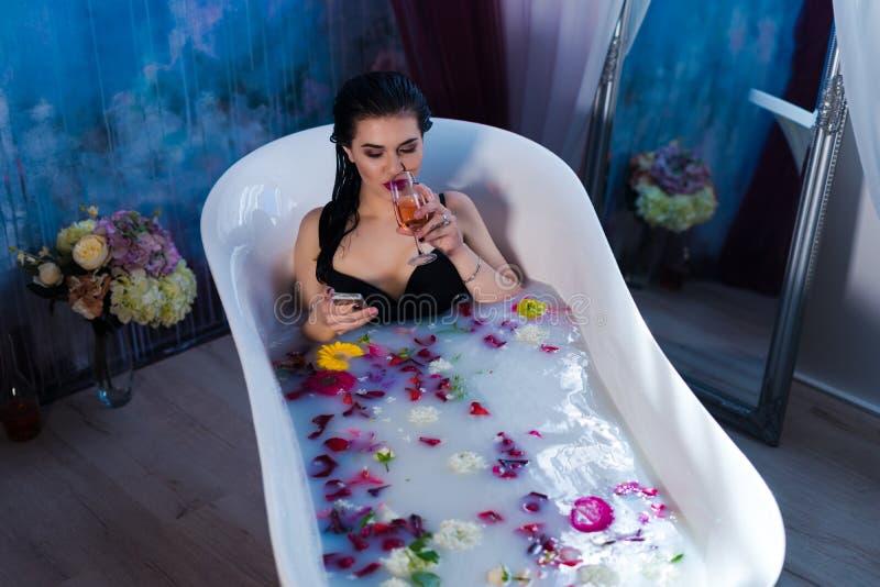 De sexy donkerbruine vrouw zit in bad en babbelt op smartphone royalty-vrije stock foto's