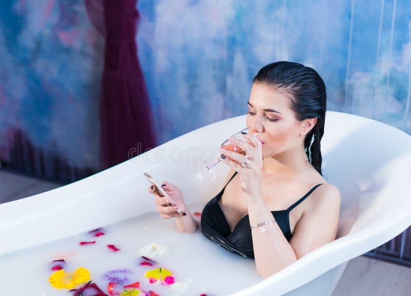 De sexy donkerbruine vrouw zit in bad en babbelt op smartphone royalty-vrije stock fotografie