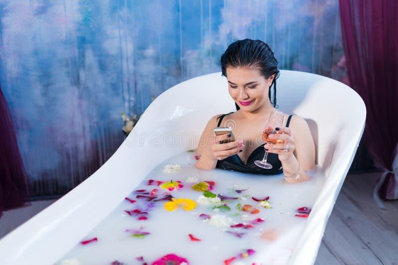 De sexy donkerbruine vrouw zit in bad en babbelt op smartphone royalty-vrije stock foto