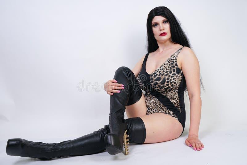 De sexy gevaarlijke donkerbruine vrouw in van het luipaardzwempak en leer dij hoge laarzen met skelet hielt op witte achtergrond  stock fotografie