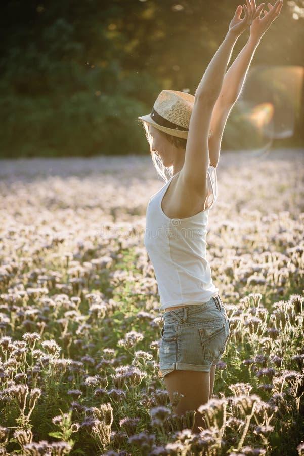 De sexy jonge vrouw geniet van zon openlucht bij bloemgebied royalty-vrije stock afbeeldingen