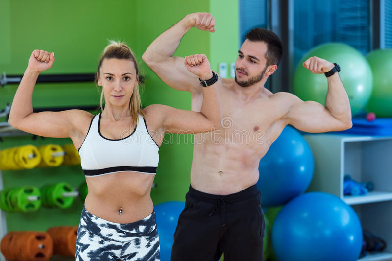 De sexy Kaukasische man en de vrouw in gymnastiekpaar leiden in geschiktheidsclub die op met wellness van de gewichtenlevensstijl royalty-vrije stock foto's