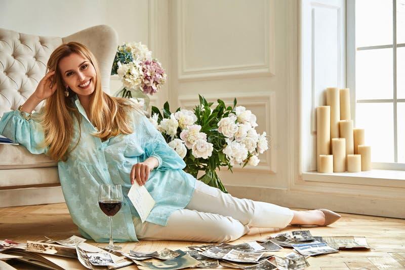 De sexy mooie blondevrouw zit op de vloer kijkt familiealbum stock foto's