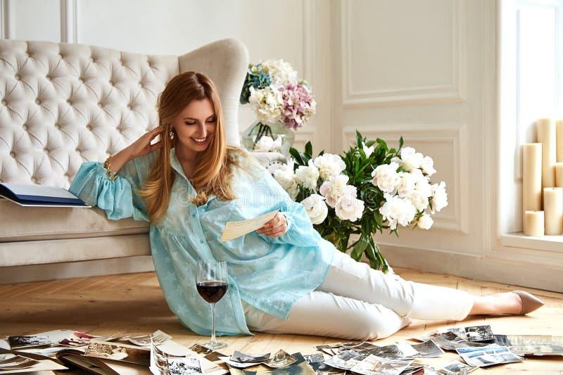 De sexy mooie blondevrouw zit op de vloer kijkt familiealbum stock afbeeldingen