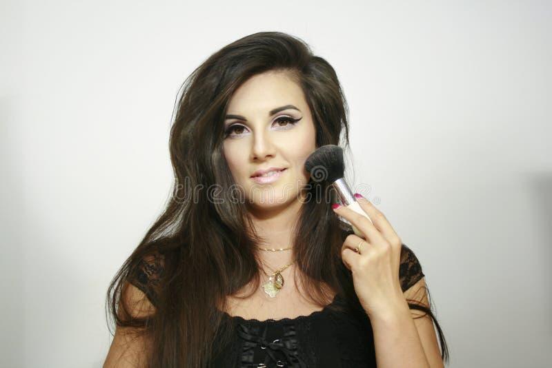 De sexy mooie het gebruiks grote pluizige borstel van het make-upmeisje, bekijkt u met lichte glimlach stock afbeeldingen