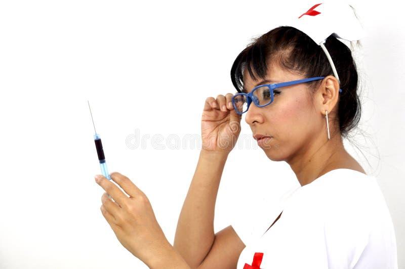De sexy verpleegster die glazen dragen houdt een spuit royalty-vrije stock fotografie
