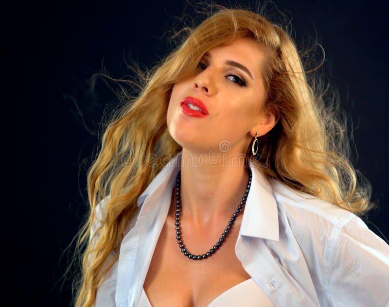 De sexy vrouw gekleed in bedrijfsstijl verleidt binnen stelt stock foto