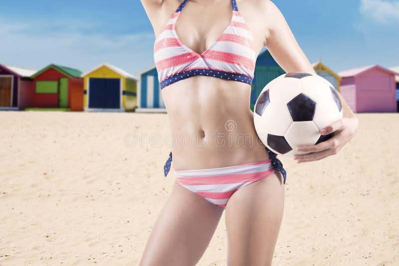De sexy vrouw houdt een voetbalbal stock afbeelding