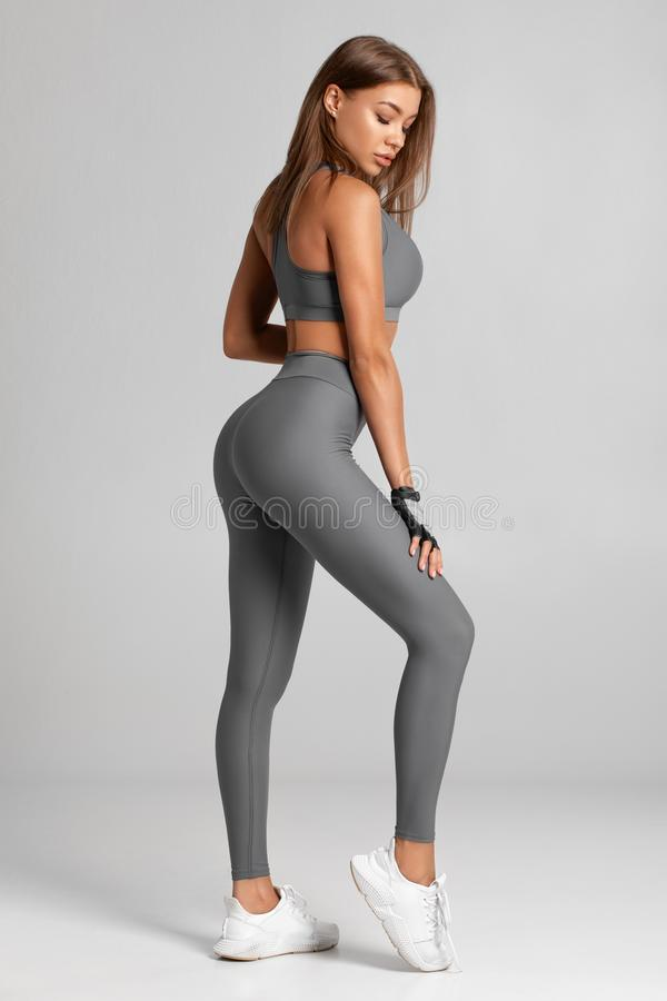 De sexy Vrouw van de Geschiktheid Mooi atletisch meisje, dat op de grijze achtergrond wordt ge?soleerd royalty-vrije stock fotografie