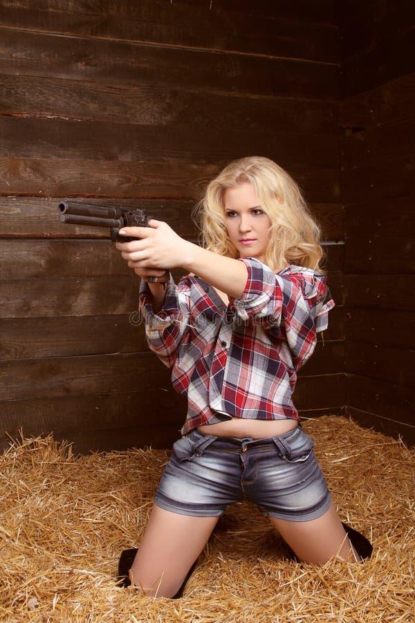 De sexy vrouw van het gevaar met revolver over stapel van strotextuur backg stock foto's