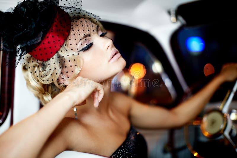 De sexy zitting van het maniermeisje in oude auto royalty-vrije stock foto