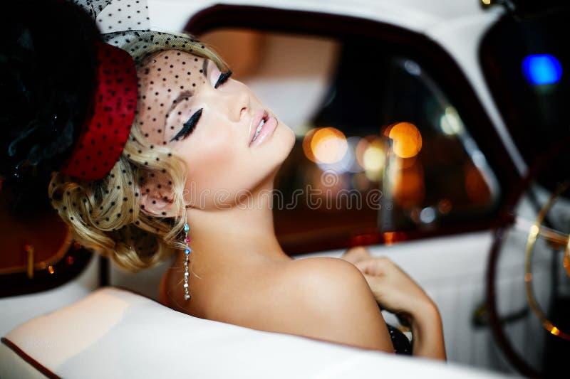 De sexy zitting van het maniermeisje in oude auto stock afbeelding