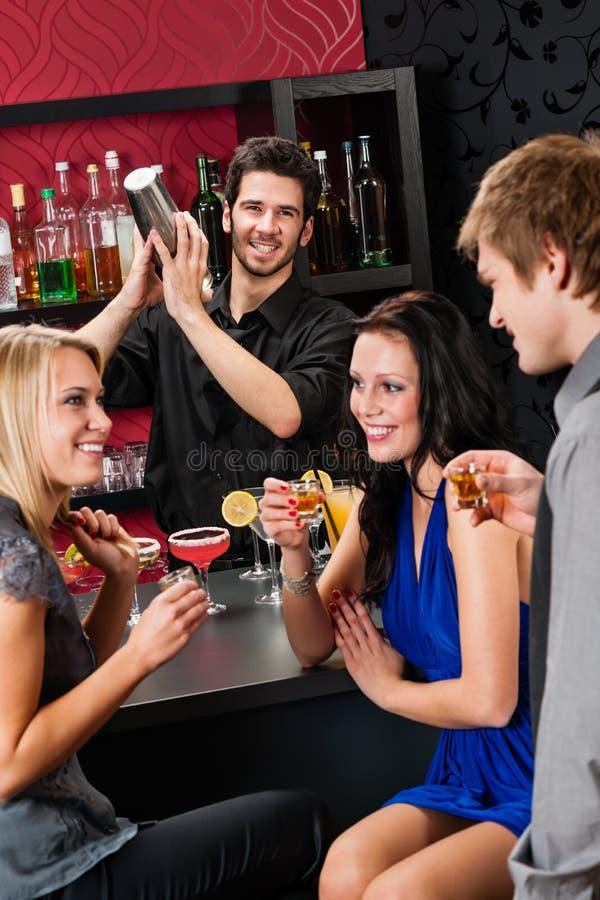 De shakervrienden die van de barman bij staaf drinken stock foto's