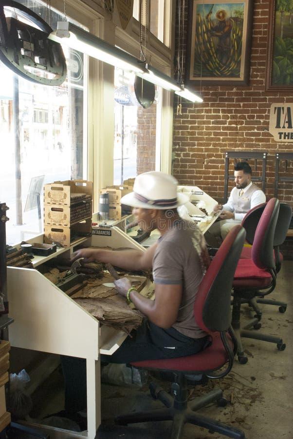 De sigarenvaklieden in de kleine sigaar winkelen werkend royalty-vrije stock afbeeldingen
