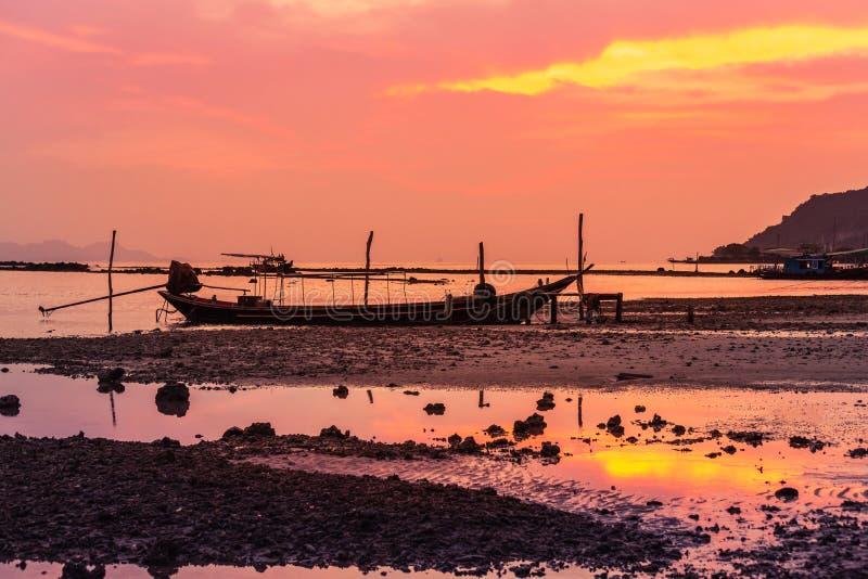 De silhouet longtail boot fishingboat legde op tropisch strand vast bij vissersdorp tijdens de tijd van de zonsondergangschemerin stock afbeelding