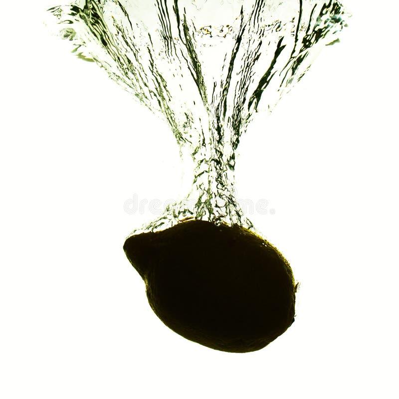 De silhouetcitroen valt in het water met plonsen, conceptenvruchten, vitaminen en gezondheid royalty-vrije stock foto's