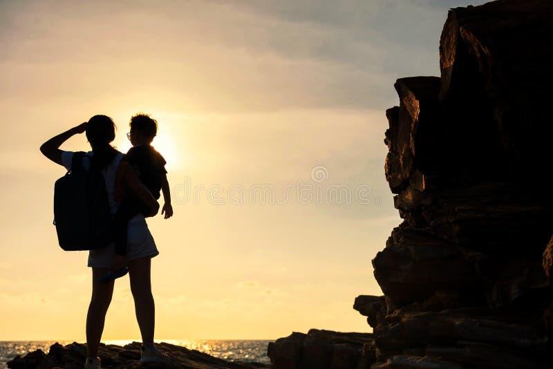 De silhouetfamilie geniet van zonsondergang en overzees royalty-vrije stock afbeelding