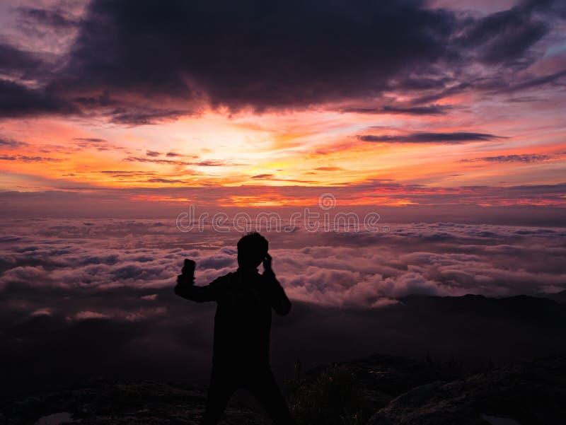De silhouetmensen nemen een Selfie op de klip met mooie zonsopganghemel op de berg van Khao Luang stock afbeelding